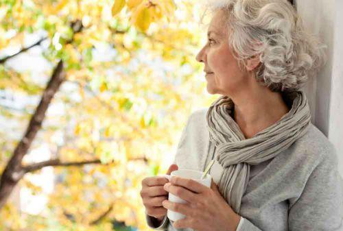 Пожилая женщина смотрит в окно